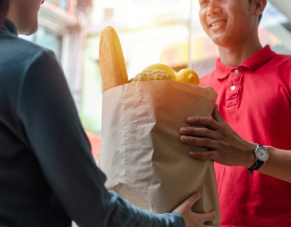 food delivery service man in red uniform smiling handing fresh food to recipient and young woman customer receiving order from courier at home, express delivery, food delivery, online shopping concept
