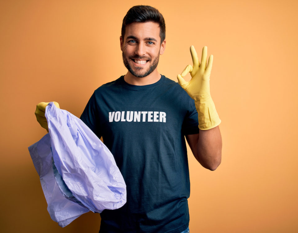 Young handsome volunteer man with beard cleaning junk using bag over yellow background doing ok sign with fingers, excellent symbol