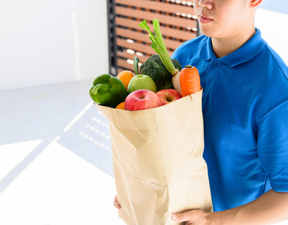 Food delivery service man in blue uniform. Thai deliveryman holding fresh food for young woman. Customer receiving order from courier at home.